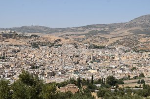 Hilltop view overlooking the old section of the ancient city of Fes, Morocco, with the rolling hills behind the city leading towards the Atlas mountains