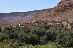 "An old populated settlement stands among a lush oasis in the beginning of the desert region of Morocco, laying between two cliffs in what is known as the ""Gate of the Sahara"" and the ""Grand Canyon of Morocco."""