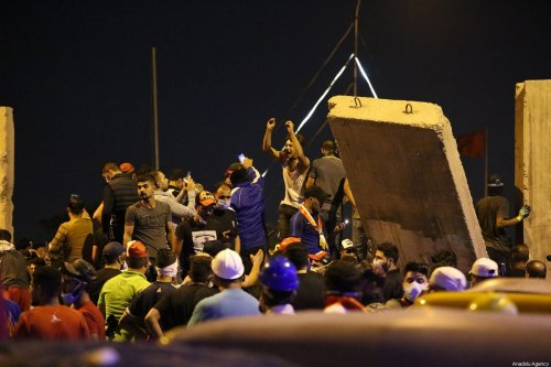 Iraqi protesters try to remove the security forces' barricades on Al-Sarafiya Bridge and try to enter the road of the high-security Green Zone, where key government offices and foreign embassies are based, during ongoing anti-government demonstrations at Tahrir Square in Iraq's capital Baghdad on October 30, 2019 [Murtadha Sudani / Anadolu Agency]