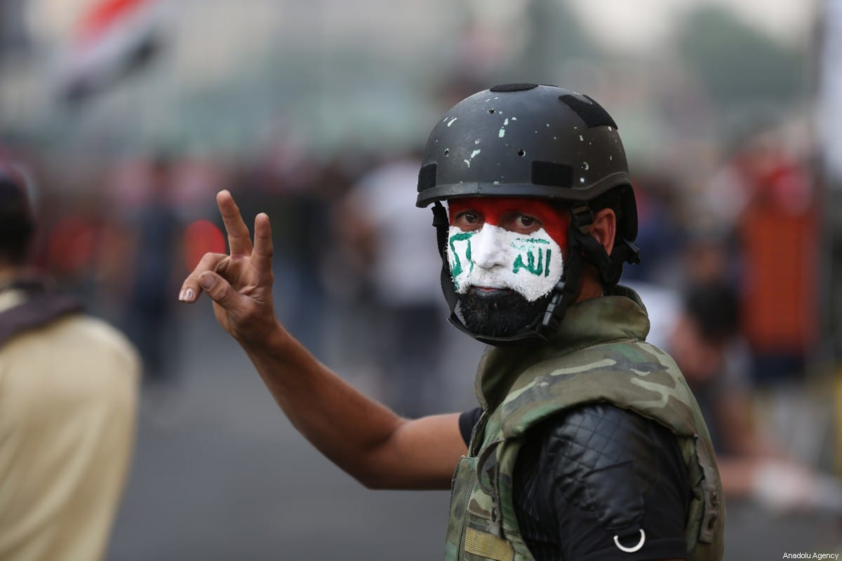 A protester flashes a sign during an anti-government protest at al-Khalani Square in central Baghdad, Iraq on 14 November, 2019 [Murtadha Sudani/Anadolu Agency]