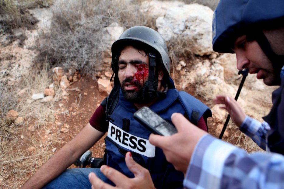 G Media photo-journalist Muath Amarneh is being carried away after being shot with rubber bullet from his eye by Israeli forces during a protest against separation wall and Jewish settlements in Hebron, West Bank on 15 November 2019. [Mamoun Wazwaz - Anadolu Agency]