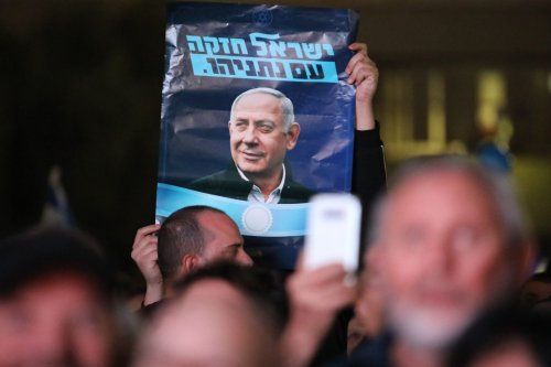 Israeli people hold placards during a demonstration in support of Israel's Prime Minister Benjamin Netanyahu in Tel Aviv, Israel on 26 November, 2019 [Mostafa Alkharouf/Anadolu Agency]