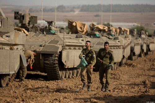 Israeli soldiers walk near an armoured perssonel carrier near the border with Gaza, in Southern Israel on November 13, 2019 in Sderot, Israel [Amir Levy/Getty Images]