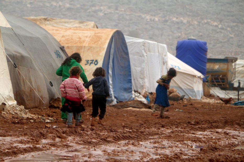 Syrian children are seen on the mud covered road between tents at a refugee camp, where Syrian refugees live, after heavy rain at winter season in northeastern Idlib, Syria on 2 December 2019. [Muhammed Abdullah - Anadolu Agency]