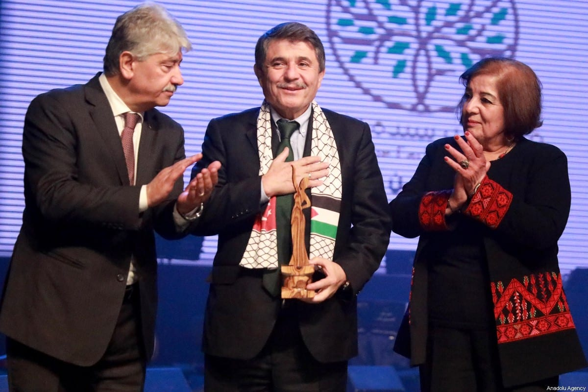 Chairman of Turkey-Palestine Friendship Group Huseyin Tanriverdi (C) receives 'Person of the Year' award during a ceremony held by The Lady of the Earth Foundation in West Bank city of Ramallah on December 21, 2019 [Issam Rimawi / Anadolu Agency]