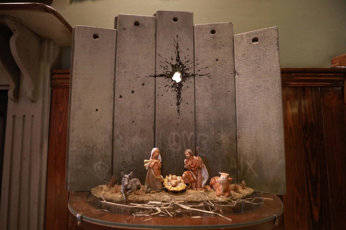"UK-based street artist Banksy's artwork named ""Scar of Bethlehem"" depicting nativity scene with Mary and Joseph and the baby Jesus in front of the Israeli separation wall is displayed at ""The Walled Off"" hotel in Bethlehem, West Bank on December 22, 2019 [Issam Rimawi / Anadolu Agency]"
