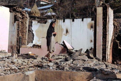 A woman stands on the debris of her house targeted by cross border Indian troops in Kashmir on 23 December 2019 [CHUDARY NASEER/Anadolu Agency]