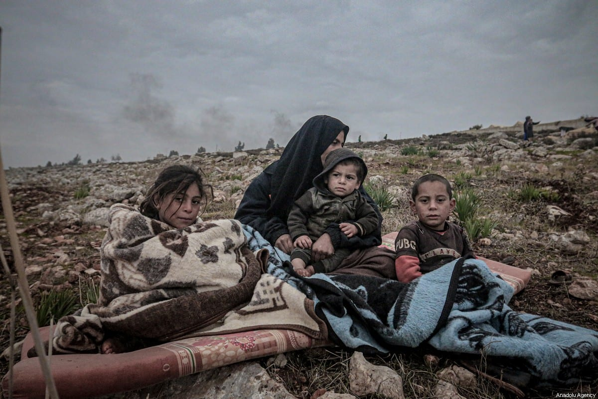 Syrians are seen with their belongings who have been forced to displace due to the ongoing attacks carried out by Assad regime and Russia, during winter season at makeshift tent area in Harbanos town of Idlib, Syria on December 24, 2019 [Muhammed Said / Anadolu Agency]