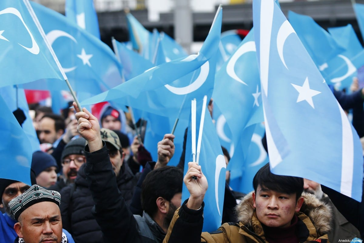 Demonstrators hold Uyghur flags as they take part in a demonstration in support of Uyghur Turks against human rights violations of China, in Berlin, Germany on 27 December 2019. [Abdulhamid Hoşbaş - Anadolu Agency]