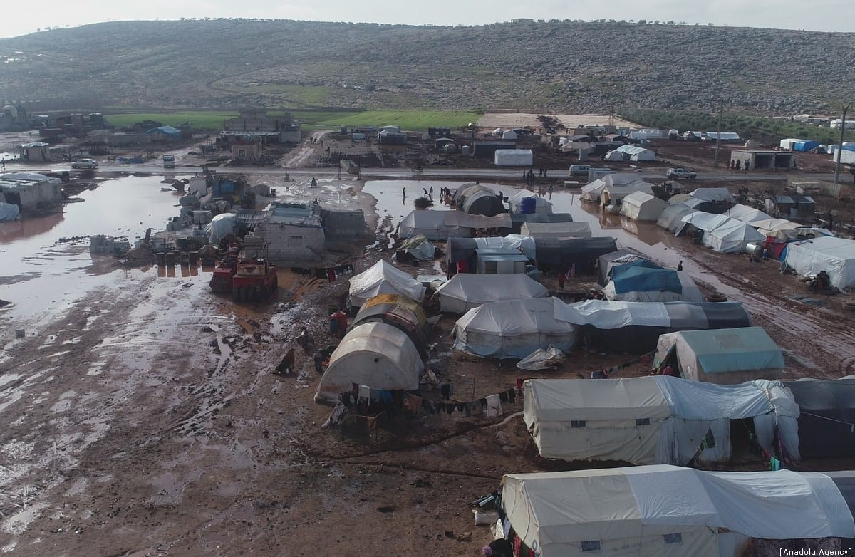 A drone photo shows tents amid mud at a refugee camp, which provides living space for Syrians those who escape from the war or displaced by the attacks of Assad Regime and Russia, as refugees leave their home to reach the Turkish border on December 30, 2019 in Idlib, Syria. [Mehmet Burak Karacaoğlu/Anadolu Agency]