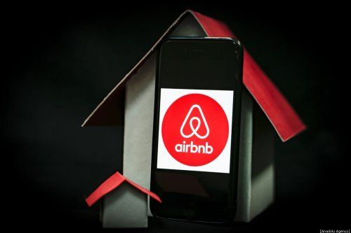 A phone screen displays logo of Airbnb with a house mock-ups next to it, on December 30, 2019 in Ankara, Turkey. [Metin Aktaş - Anadolu Agency]