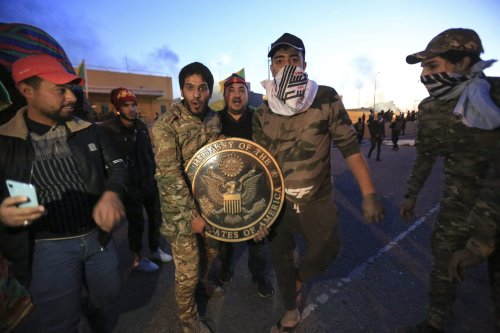Outraged Iraqi protesters pose for a photo with US Embassy plaque as they storm the US Embassy in Baghdad, protesting Washington's attacks on armed battalions belong to Iranian-backed Hashd al-Shaabi forces on 31 December, 2019 [Murtadha Sudani/Anadolu Agency]