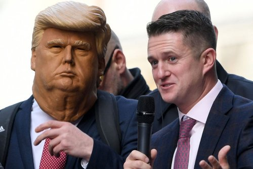 Stephen Yaxley-Lennon (R), AKA Tommy Robinson, founder and former leader of the anti-Islam English Defence League (EDL), addresses supporters, one wearing a mask of US President Donald Trump (L), outside the Old Bailey, London's Central Criminal Court, in central London on October 23, 2018 [CHRIS J RATCLIFFE/AFP via Getty Images]