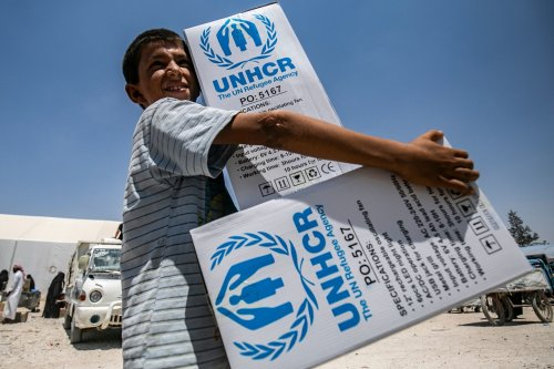 A boy walks carrying packages of humanitarian aid at al-Hol camp for displaced people in al-Hasakeh governorate in northeastern Syria on July 22, 2019, as people collect UN-provided humanitarian aid packages. [Delil Souleiman /AFP/Getty Images]