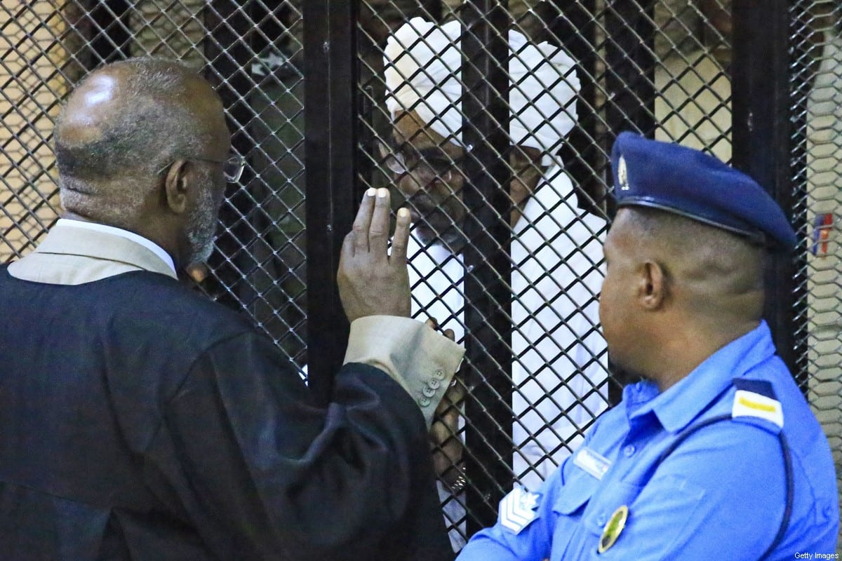 Sudan's deposed military president Omar al-Bashir sits in a defendant's cage during his corruption trial at a court in Khartoum on 14 December 2019. [AFP via Getty Images]