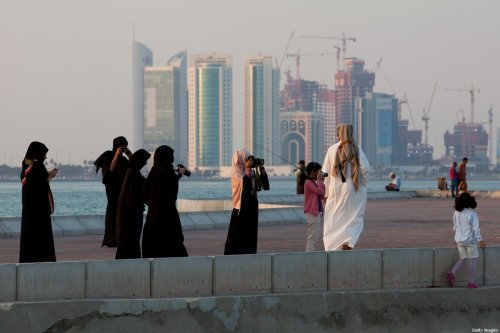 New high-rise office buildings and hotels, some of them still under construction, stand in the West Bay and Oneiza district near City Center mall and build the skyline at the opposite of the promenade at the Al Corniche road are photographed by Qatari people in their traditional clothes called dishdasha (man) and abaya (woman) on December 21, 2011 in Doha, Qatar [Nadine Rupp/Getty Images]