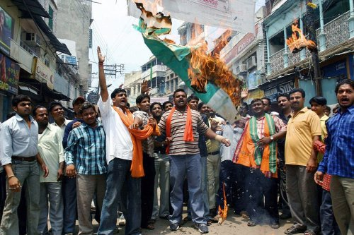 Indian activists from the Hindu nationalist party Shiva Sena, shout slogans as they burn a Pakistani flag near the Kashi Vishwanath Temple in Varanasi, 6 July 2005 [STR/AFP/Getty Images]