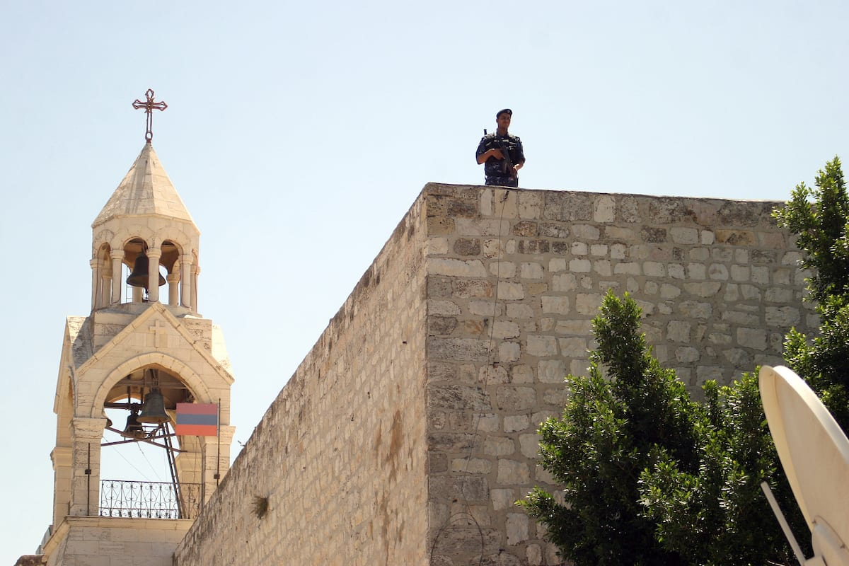 Palestinian security forces stand guard on the roof of the Church of Nativity in Bethlehem's Manger Square during the arrival of the participants in the sixth conference of Fatah movement in the West Bank city of Bethlehem on 5 August, 2009 [Najeh Hashlamoun/Apaimages]