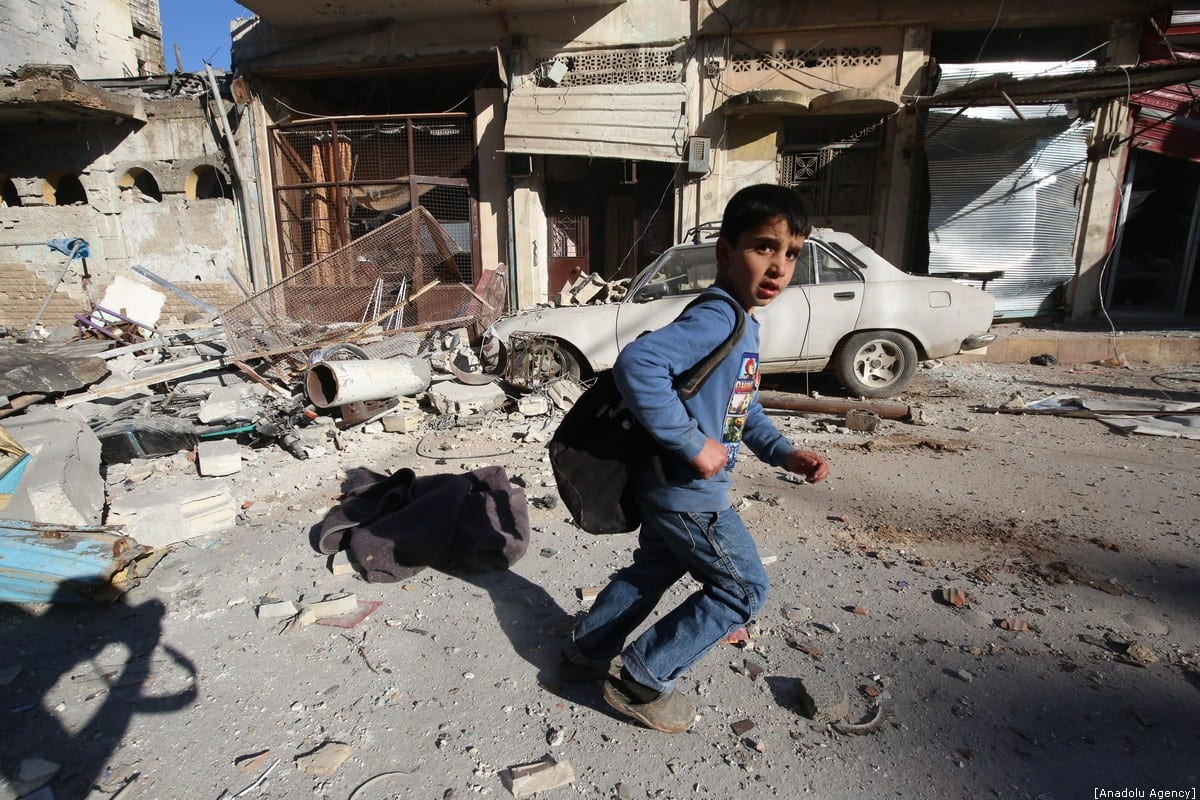 A child runs away after airstrikes of Assad regime hit Binnish village in Idlib, Syria on January 11, 2020. At least 17 civilians were reported dead. [Izzeddin İdilbi/Anadolu Agency]