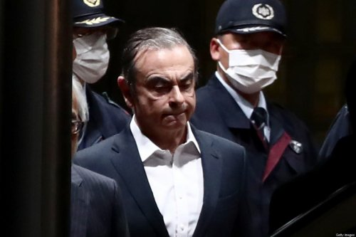 Former Nissan chairman Carlos Ghosn (C) is escorted as he walks out of the Tokyo Detention House following his release on bail in Tokyo on April 25, 2019 [BEHROUZ MEHRI/AFP via Getty Images]