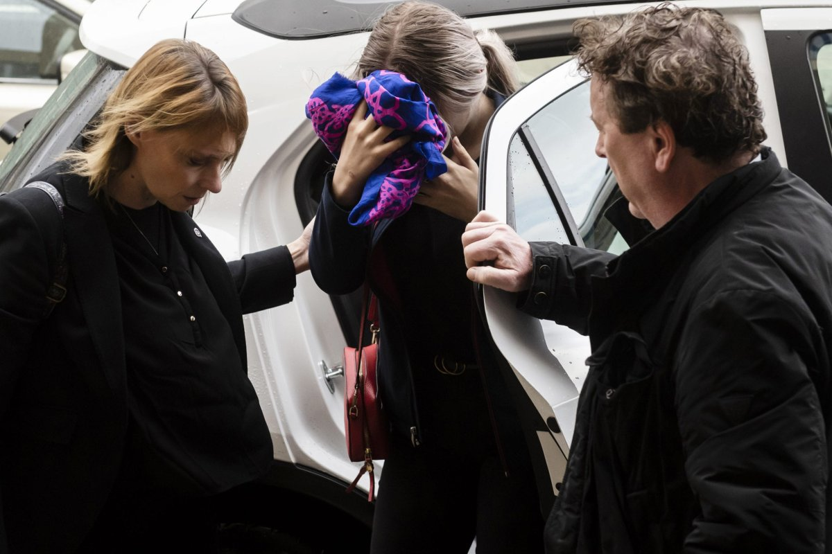 A British teenager (C) accused of falsely claiming she was raped by Israeli tourists, covers her face as she arrives for her trial at the Famagusta District Court in Paralimni in eastern Cyprus, on December 30, 2019.[IAKOVOS HATZISTAVROU/AFP via Getty Images]