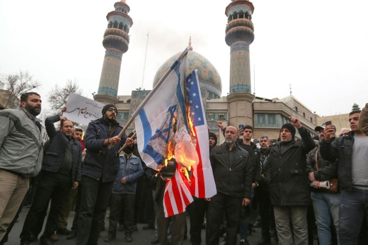 Iranians burn US and Israeli flags during an anti-US protest over the killings during a US air stike of Iranian military commander Qasem Soleimani and Iraqi paramilitary chief Abu Mahdi al-Muhandis, in the capital Tehran on 4 January, 2020 [ATTA KENARE/AFP via Getty Images]