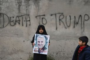 A Shia Muslim girl holds a poster of Iranian commander Qasem Soleimani as she takes part in a anti-US protest against the killing of top Iranian commander Qasem Soleimani in Iraq, in Lahore on 12 January, 2020 [ARIF ALI/AFP via Getty Images]