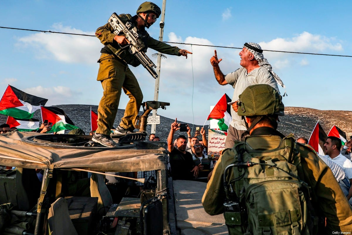 A Palestinian protester yells at an Israeli soldier as he confronts him atop an Israeli army vehicle during a protest against Israeli forces conducting an exercise in a residential area near the Palestinian village of Naqura, northwest of Nablus in the occupied West Bank, on September 4, 2019 (Photo credit should read [JAAFAR ASHTIYEH/AFP via Getty Images]