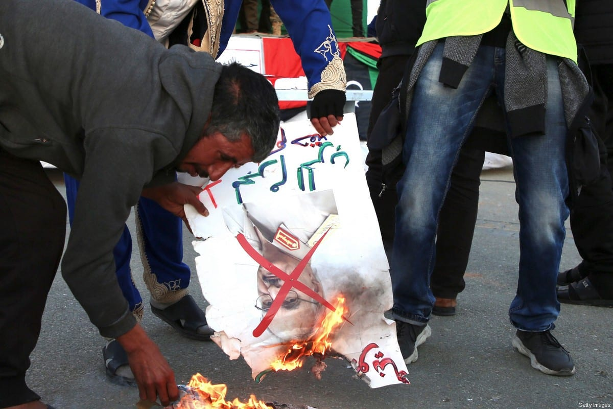 Libyans burn a picture of strongman Khalifa Haftar during a rally in support of the UN-recognised Tripoli-based government (GNA), in the capital Tripoli on January 3, 2020. (Photo by - / AFP) (Photo by -/AFP via Getty Images)