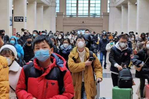 People wear face masks as they wait at Hankou Railway Station in Wuhan, China on 22 January 2020 [Getty Images]