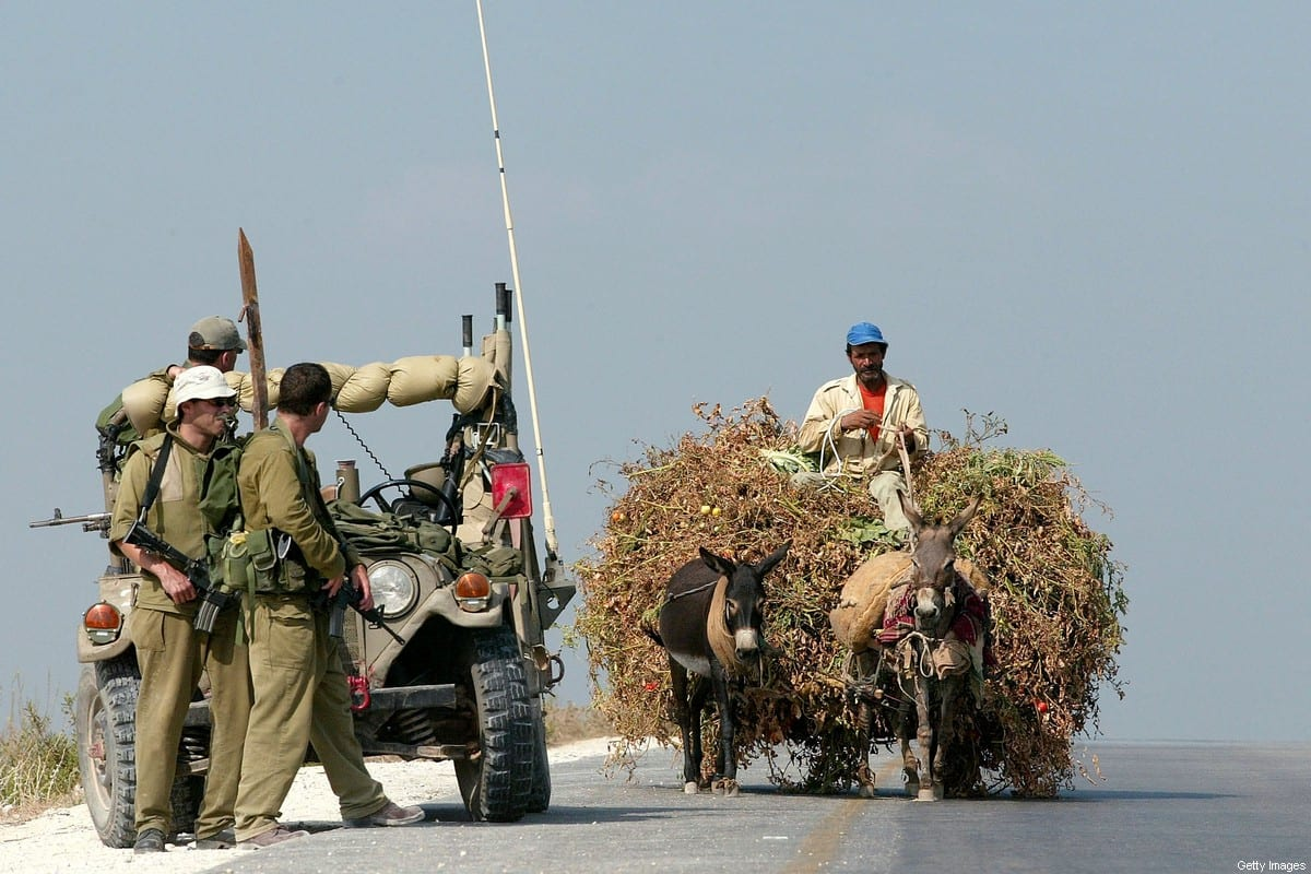 A Palestinian man uses a donkey cart to transport animal fodder for his herd as he passes Israeli soldiers guarding the road August 6, 2002 around the West Bank town of Qalqilya [David Silverman/Getty Images]
