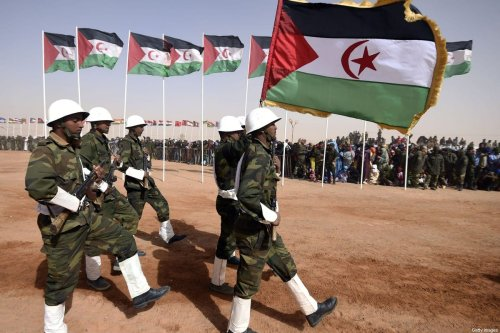 Members of the Sahrawi People's Liberation Army parade with Polisario Front's flags in the disputed territory of Western Sahara on 27 February 2016 at the Sahrawi refugee camp of Dakhla which lies 170 km to the southeast of the Algerian city of Tindouf. [FAROUK BATICHE/AFP via Getty Images]