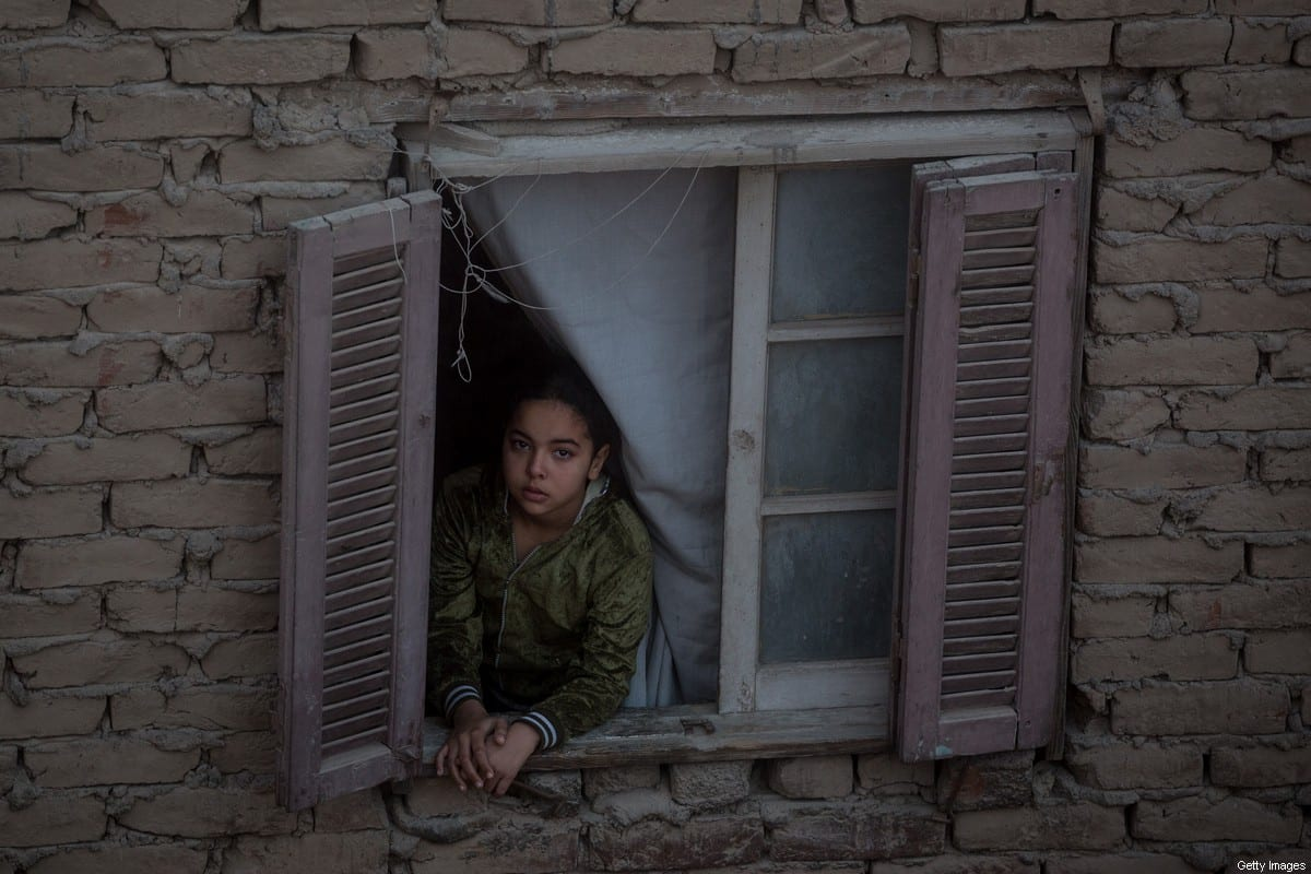 """A young girl looks out of her window in an building inside the famous """"City of the Dead """" neighbourhood on December 15, 2016 in Cairo, Egypt. The """"City of the Dead"""" houses more than half a million people living inside the graveyard. [Chris McGrath/Getty Images]"""
