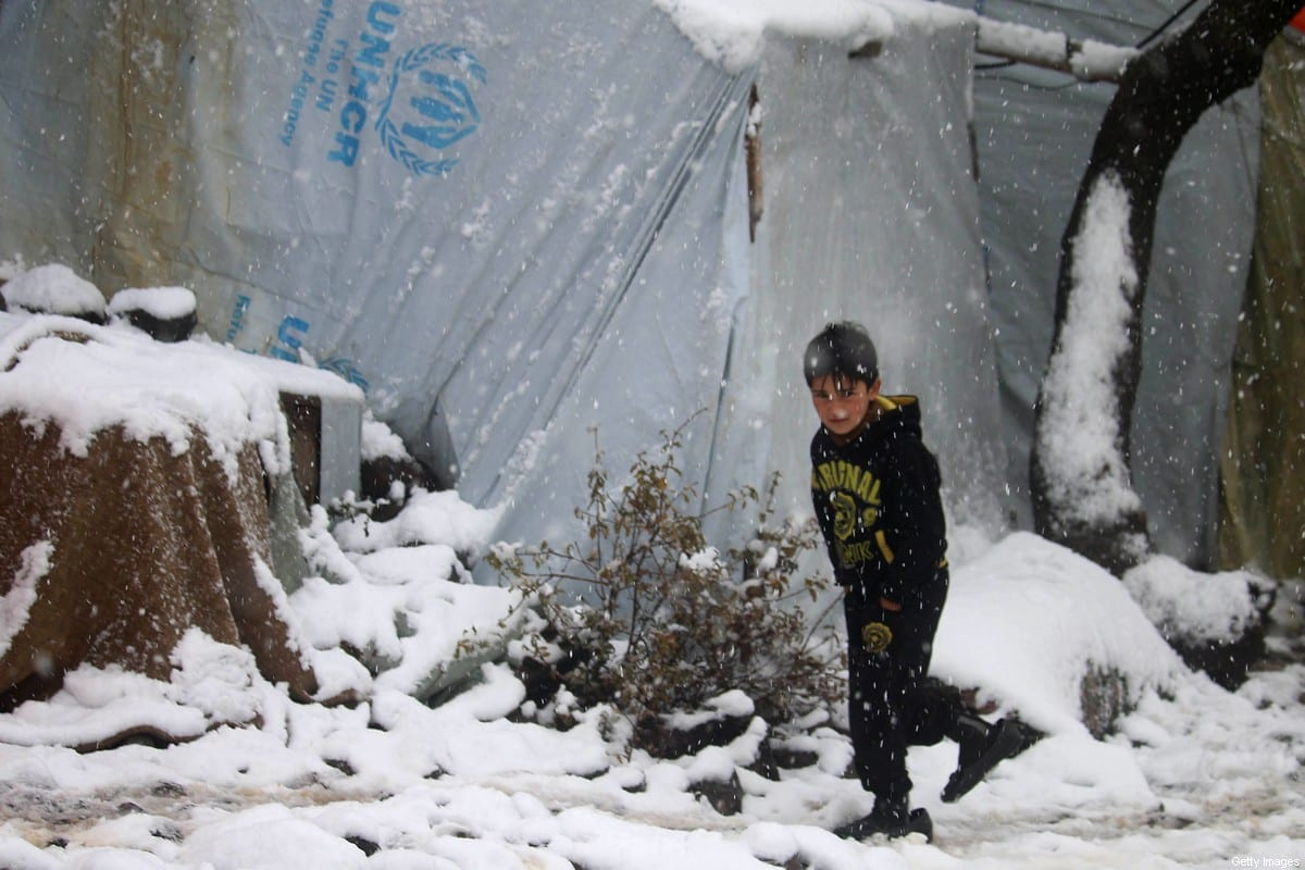 TOPSHOT - A displaced Syrian child walks through a blizzard at a make-shift refugee camp near the village of Burayqah on the outskirts of southeastern Syrian border town of Quneitra, on January 26, 2018. / AFP PHOTO / Mohamad ABAZEED (Photo credit should read MOHAMAD ABAZEED/AFP via Getty Images)
