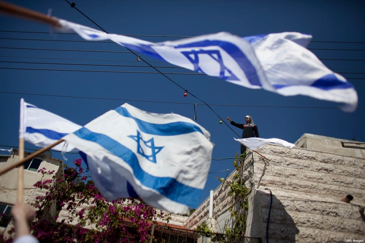 An Arab woman waves from the roof of her home as right-wing nationalist Israelis march through the Arab east Jerusalem neighbourhood of Silwan under heavy Israeli police protection on April 25, 2010 in east Jerusalem [Uriel Sinai / Getty Images]