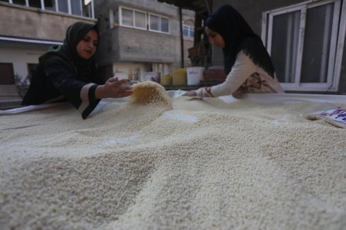 Palestinian women sift flour in preparation to make maftool in Gaza, 26 February 2020 [Mohammed Asad/Middle East Monitor]