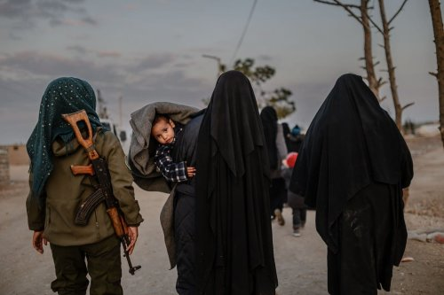 Women, reportedly wives and members of Daesh, walk under the supervision of a female fighter from the Syrian Democratic Forces (SDF) at Al-Hol camp in Syria on 17 February 2019 [BULENT KILIC/AFP/Getty Images]