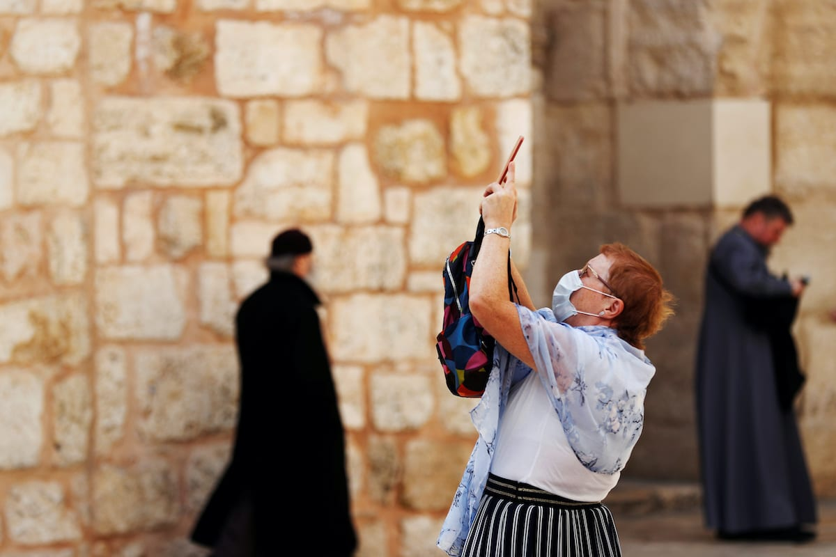 A worshiper wears a face mask for protection releted to the coronavirus as she takes a picture at the entrance to the Church of the Holy Sepulchre in Jerusalem's Old City 9 March 2020 [REUTERS/ Ronen Zevulun]