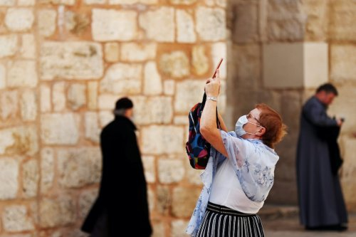 A visitor wearing a facemask, as a protection to coronavirus, seen at the entrance to the Church of the Holy Sepulchre in Jerusalem's Old City 9 March 2020 [REUTERS/ Ronen Zevulun]