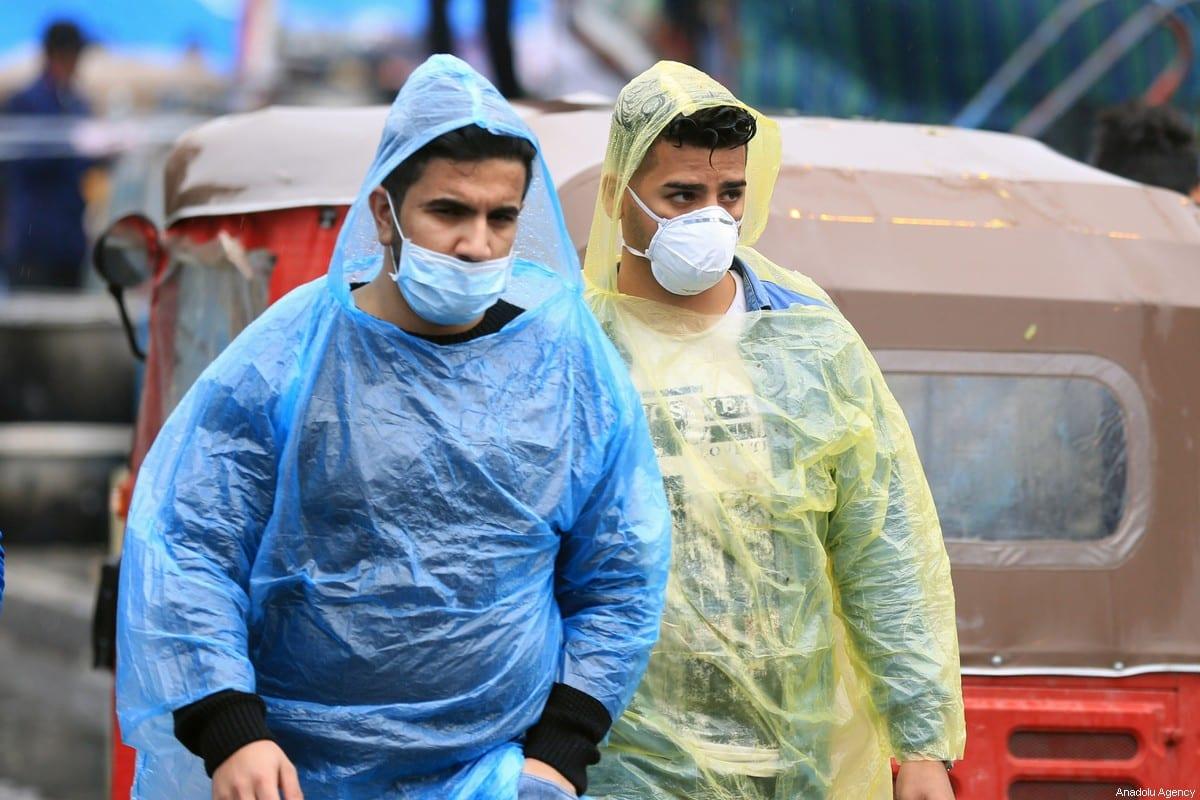 Two men wear a medical mask as a precaution against coronavirus in Baghdad, Iraq on February 25, 2020. [Murtadha Al-Sudani - Anadolu Agency]