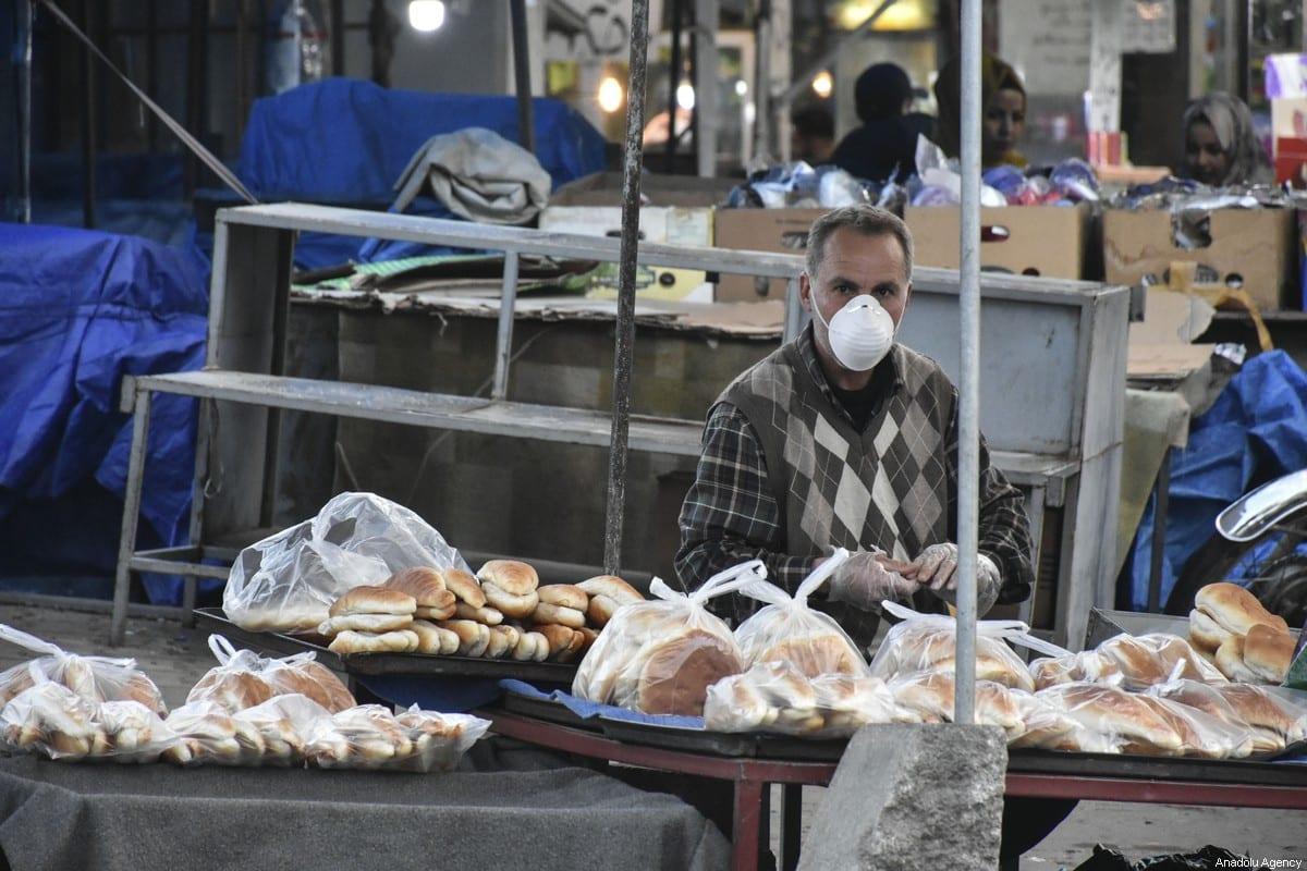 A seller wears a medical mask as a precaution due to the coronavirus outbreak in Kirkuk, Iraq on 25 February 2020 [Ali Makram Ghareeb/Anadolu Agency]