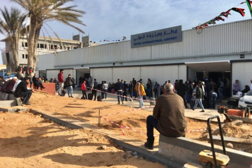 People wait in front of Mitiga International Airport in Tripoli, Libya on 27 February 2020 [Hazem Turkia/Anadolu Agency]