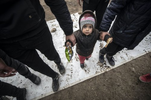 Asylum seekers leave their foot prints to painter Ahmet Dilek's canvas, which will be displayed in European countries to create awareness for the situation of the asylum seekers at the border, in Edirne, Turkey on 5 March 2020. [Şebnem Coşkun - Anadolu Agency]