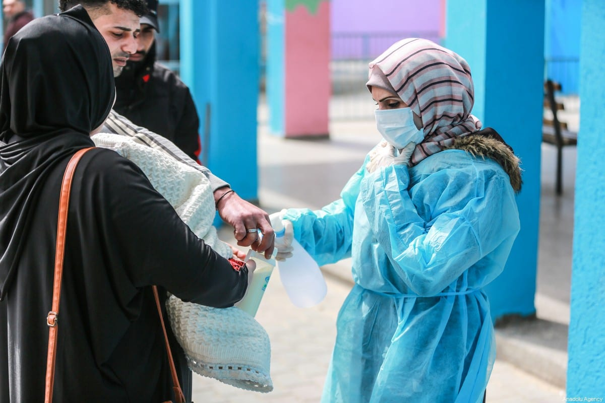A healthcare worker gives hand sanitizer to people in Gaza City, Gaza on 18 March, 2020 [Ali Jadallah/Anadolu Agency]