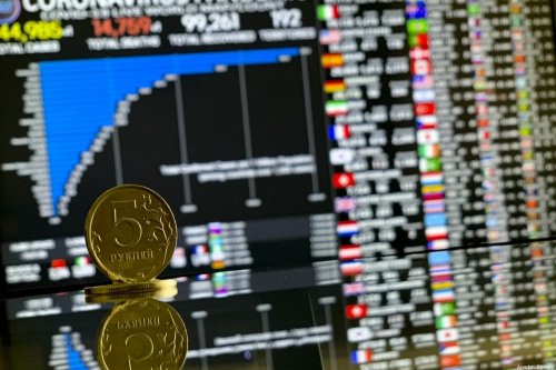 A 5 Russian Ruble coin is seen with a stock market board in back of it on March 23, 2020 in Moscow, Russia [Sefa Karacan / Anadolu Agency]