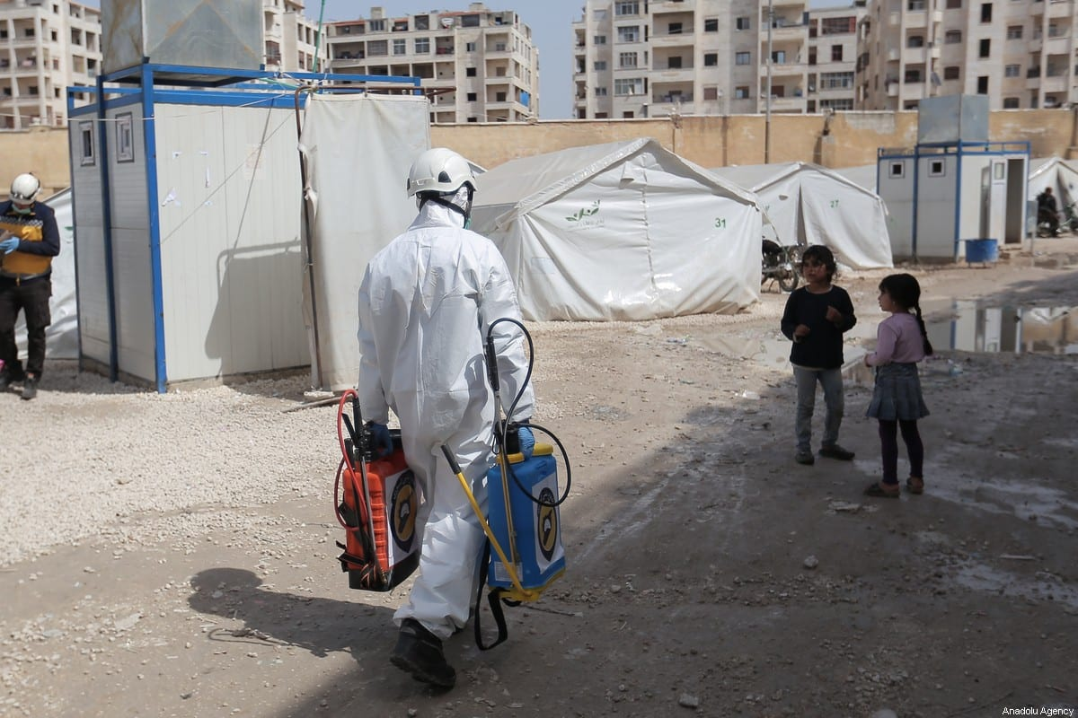 Members of the Syrian Civil Defence (White Helmets) disinfect buildings and tents where families live collectively as a preventive measure against coronavirus (Covid-19) pandemic in Idlib, Syria on 24 March 2020. [Muhammed Said - Anadolu Agency]