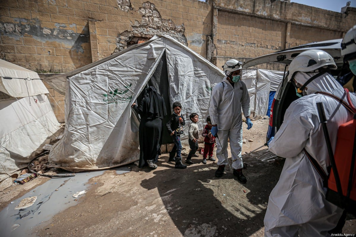 Members of the Syrian Civil Defence (White Helmets) disinfect buildings and tents where families live collectively as a preventive measure against coronavirus (Covid-19) pandemic in Idlib, Syria on 24 March 2020 [Muhammed Said/Anadolu Agency]