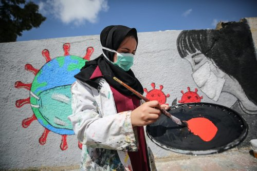 Palestinian artists paint a mural to promote protection measures against the coronavirus (COVID-19) pandemic in Khan Yunis, Gaza on March 28, 2020 [Mustafa Hassona / Anadolu Agency]