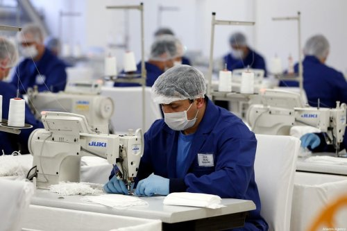 Personnels wearing face masks and gloves make production of protective face masks against the spread of novel coronavirus (COVID-19) pandemic with the instruction of Turkish Interior Minister Suleyman Soylu at the sewing workshops linked to Gendarmerie General Command of Turkey in Ankara on 29 March, 2020 [Mustafa Murat Kaynak/Anadolu Agency]