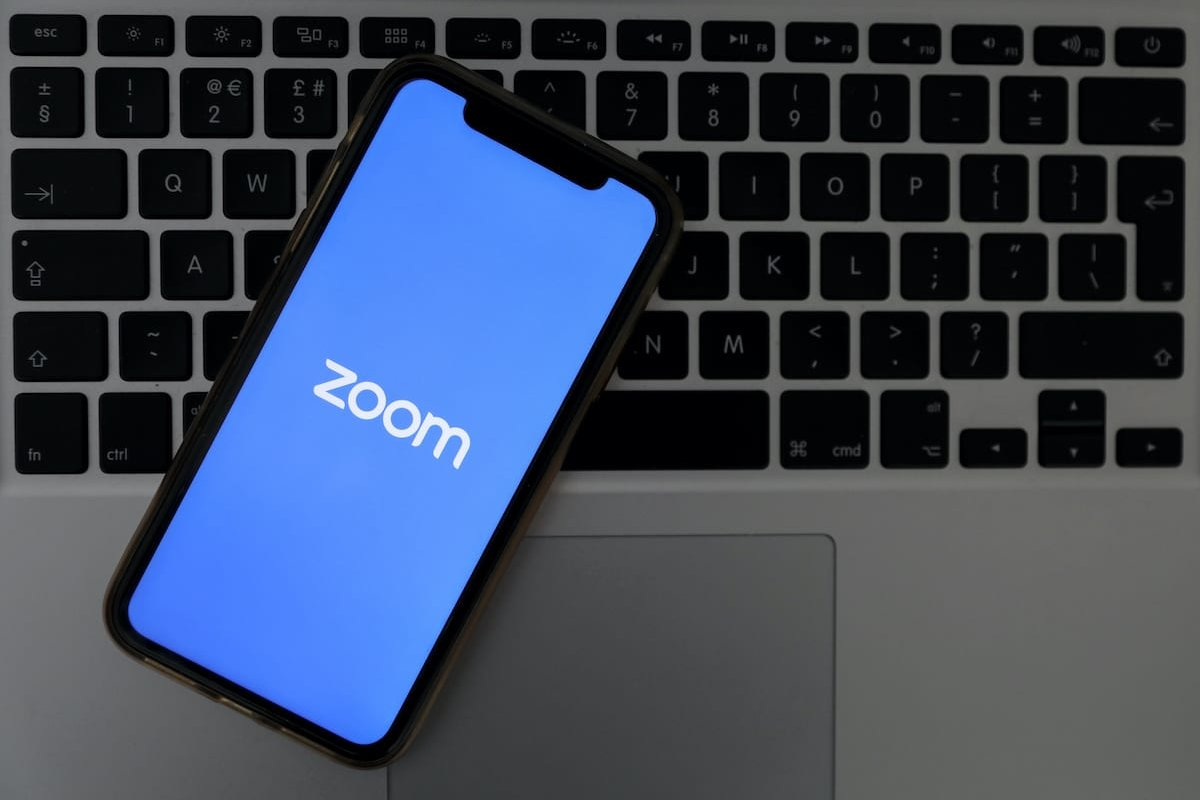 Logo of Zoom, remote conferencing services company for mobile application and desktop is seen with writing of COVID-19 coronavirus disease in back of it, in Ankara, Turkey on March 30, 2020 [Hakan Nural - Anadolu Agency]